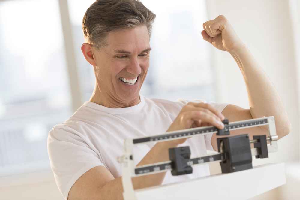 man on scale celebrating successful weight loss