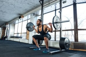 fit guy who uses Progentra doing barbell squats in the gym