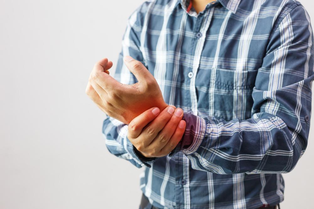 man with wrist pain due to Rheumatoid Arthritis