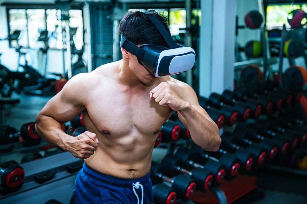man wearing VR glasses while working out gamifies fitness