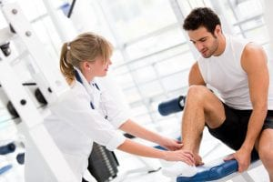 man with injured ankle attended by doctor in gym