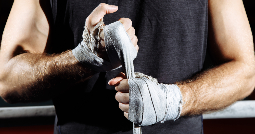 man preparing for training after injury wrapping hands