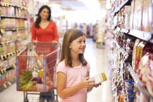 mom letting young girl help pick grocery