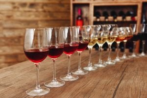 glasses of different types of wine at a bar