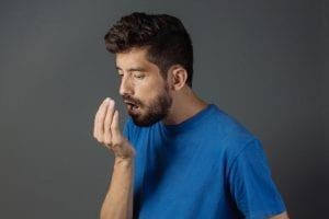 man checking himself for bad breath