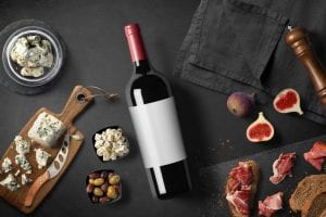 bottle of red wine with various cheese and meat cuts