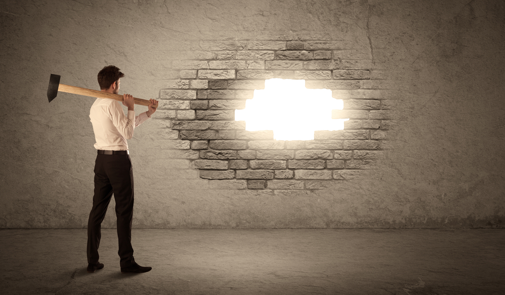 man breaks a wall with sledgehammer to reveal light representing opportunity