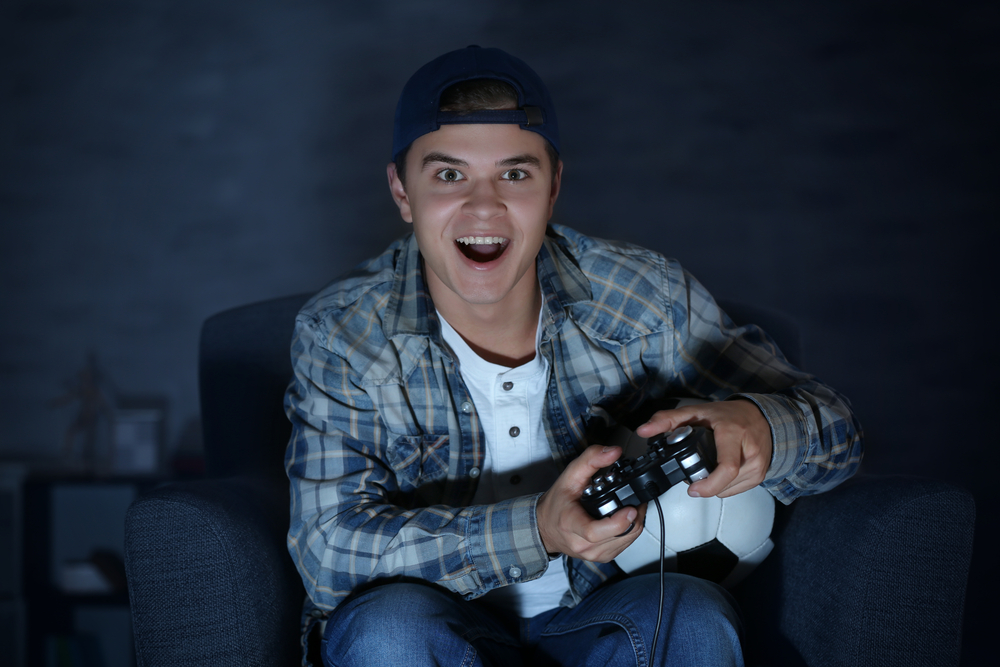 teen addicted to video game playing intently at night