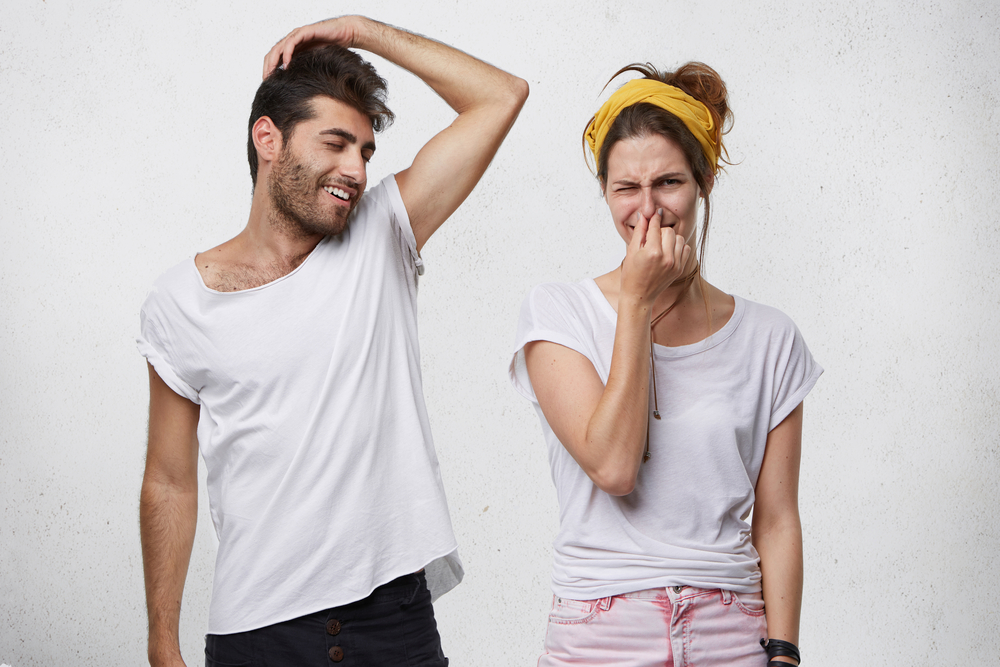 woman covering her nose next to man with smelly armpits