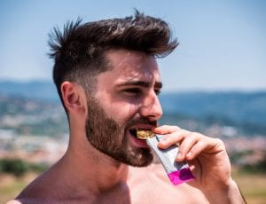 a guy eating protein bar