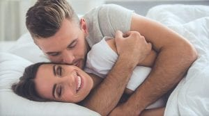 man kissing her partner while in bed