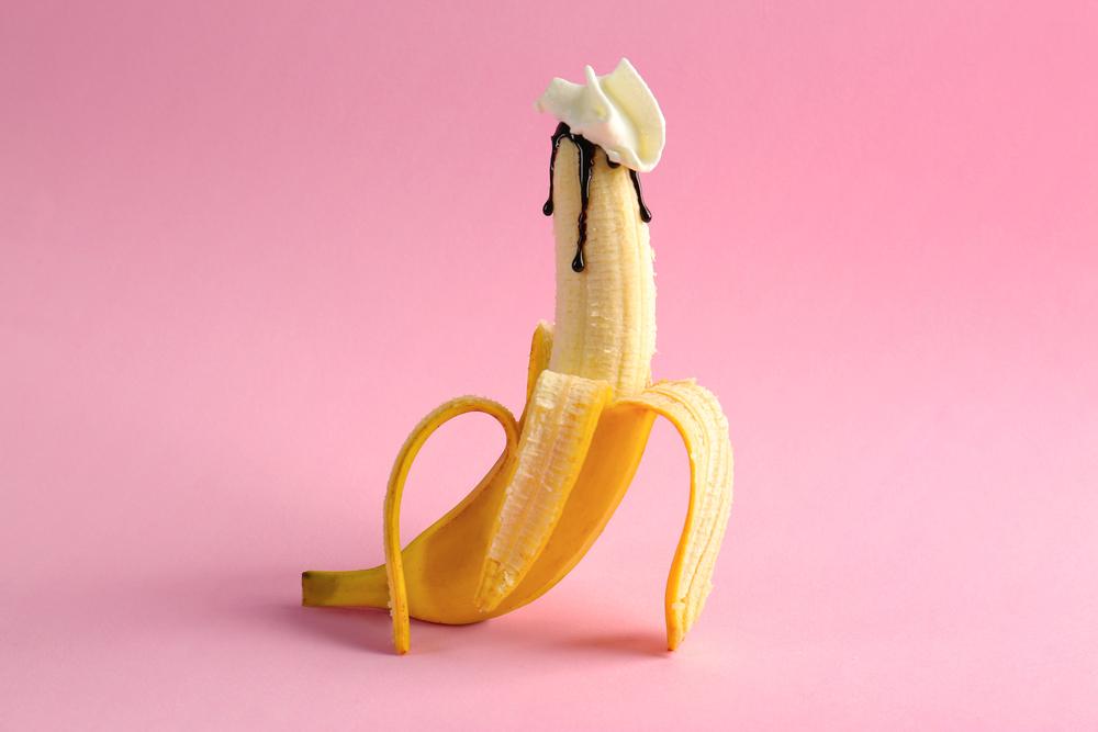 peeled banana with chocolate syrup and cream