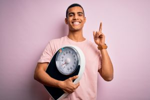 man holding a weighing scale